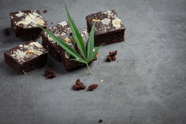 暗い床に置かれた大麻ブラウニーと大麻の葉