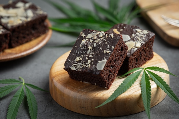 Cannabis brownies and cannabis leaves put on wooden cutting board