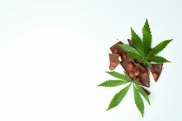 Cannabis chocolate and leaves on white background