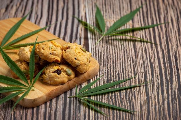 대마초 쿠키와 대마초 잎 나무 커팅 보드에 넣어