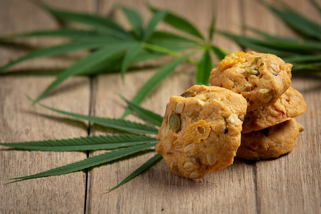 대마초 쿠키와 대마초 잎이 나무 바닥에 놓여 있습니다.