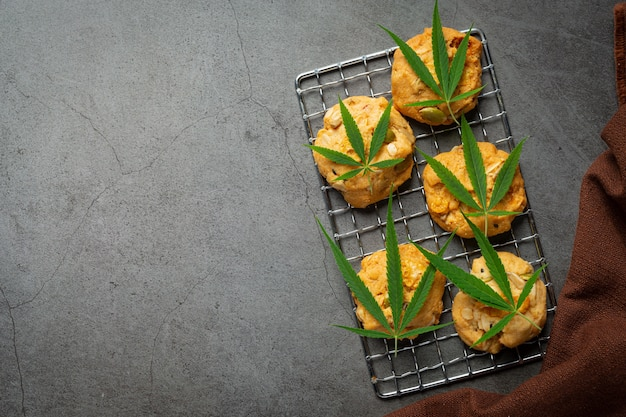 Cannabis cookies and cannabis leaves put on dark floor