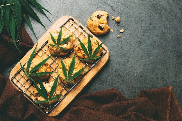 Cannabis cookies and cannabis leaves put on wooden cutting board