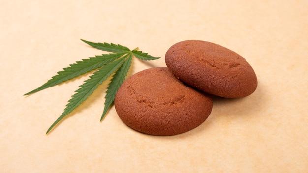 大麻クッキー、緑の葉のマリファナ、お菓子の食べ物をクローズアップ。