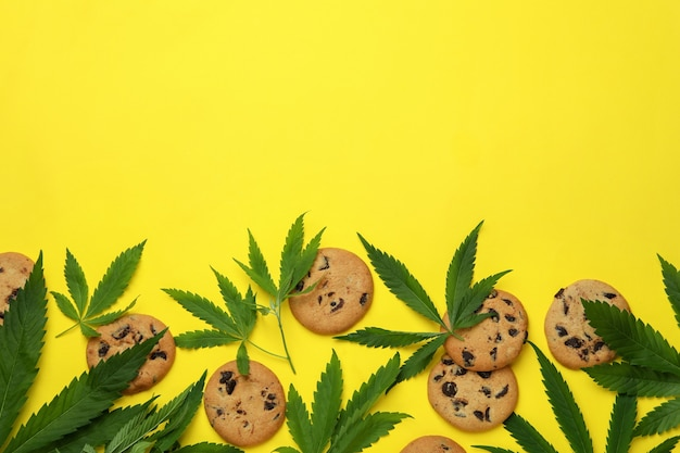 Cannabis cookies and leaves on yellow background