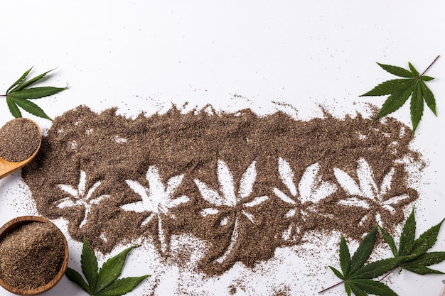 Cannabis food concept, sprinkled bran from seed cannabis, white background with hemp leaves, horizontal orientation