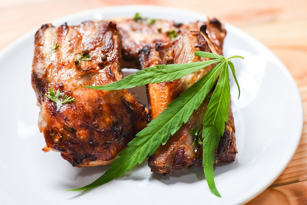 Cannabis food with bbq pork ribs grilled herbs spices served roasted barbecue pork spare rib marijuana leaf