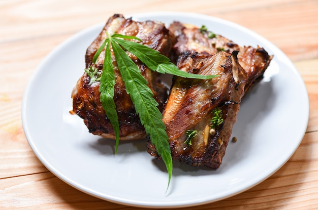 Cannabis food with bbq pork ribs grilled with herbs spices served on white plate
