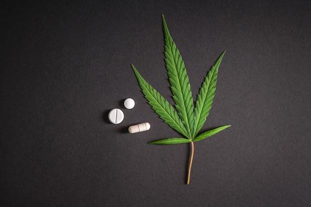 Листья каннабиса и медицинские таблетки, наркотики, марихуана, изолированные на черной поверхности.