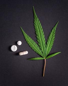Лист каннабиса и медицинские таблетки, наркотики, марихуана