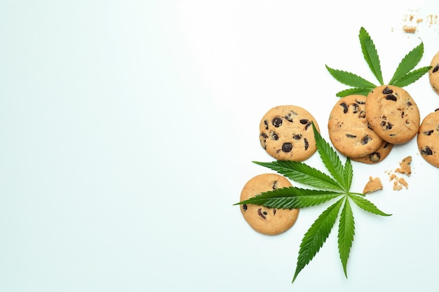 Cannabis leaves and cookies on white