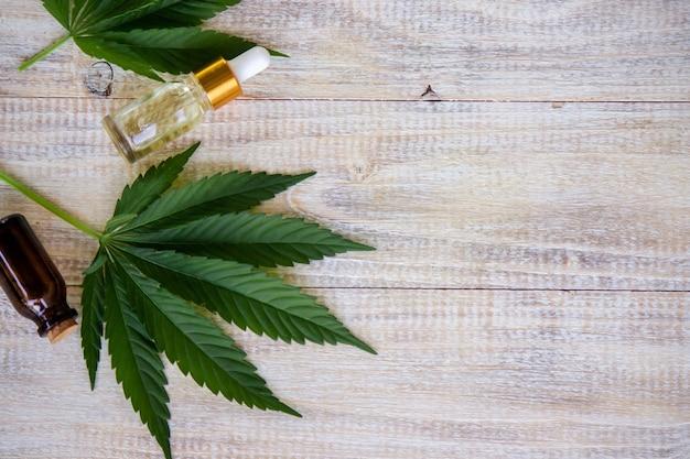 대마초는 병, 대마초 기름과 함께 나무 배경에 나뭇잎. 선택적 초점