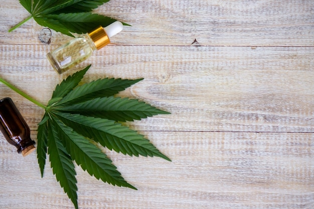 Cannabis leaves on wood background with bottles, cannabis oil. selective focus