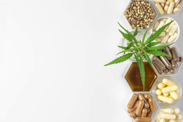 大麻薬のカプセル、ヘンプオイルと種子、白い背景の上のハニカムジャーの緑の植物