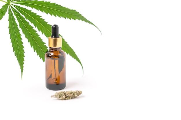 항아리에 있는 대마초 오일 추출물과 녹색 대마초 잎, 흰색 배경에 격리된 마리화나. 성장하는 의료 및 허브 마리화나.