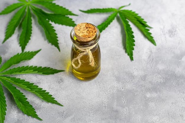 灰色の背景に透明なボトルと麻の葉の大麻油。