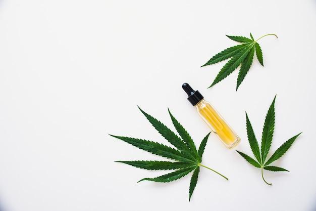 緑の葉とスポイトボトルの大麻油。代替医療の概念。