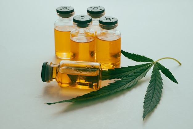 白い背景の上の緑の葉とバイアルの大麻油。代替医療の概念。
