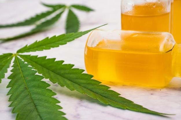 大理石のテーブルに緑の葉が付いているバイアルの大麻油。代替医療の概念。