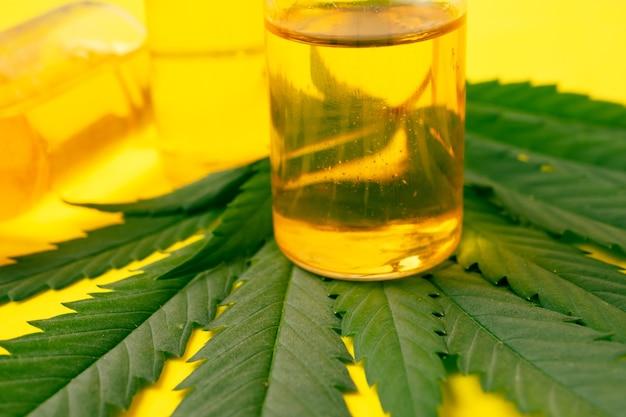 黄色の背景に緑の葉を持つバイアルの大麻油。代替医療の概念。