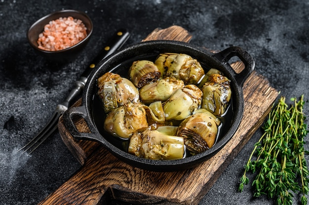 Canned artichokes in olive oil on a rustic wooden kitchen table.