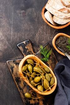 Консервированные каперсы в деревянной тарелке, тапенад и хлеб на модном темном деревянном старом фоне. вид сверху