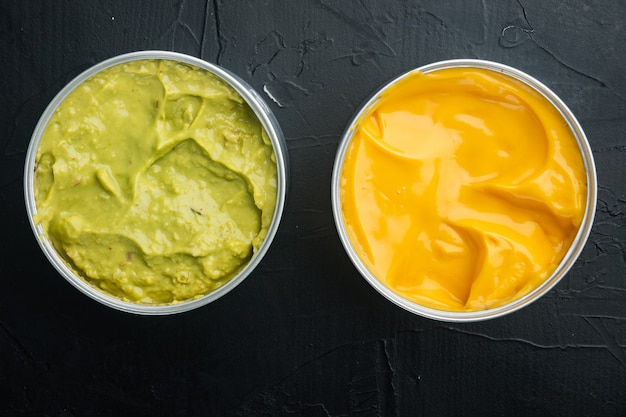 Canned cheese and guacamole  sauce in can, on black table, top view or flat lay