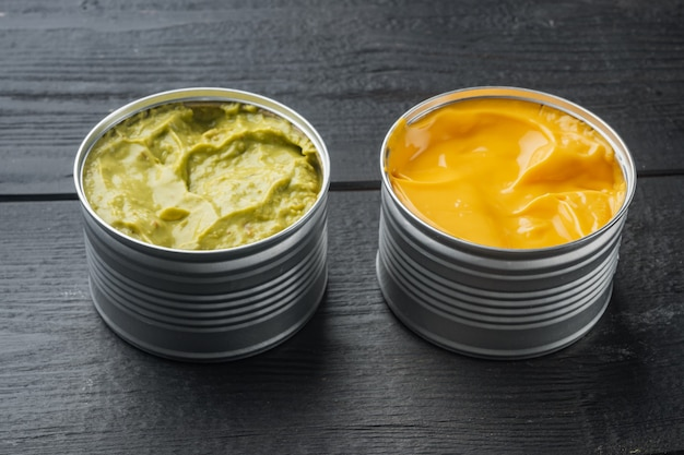 Canned cheese and guacamole  sauce in can, on black wooden table