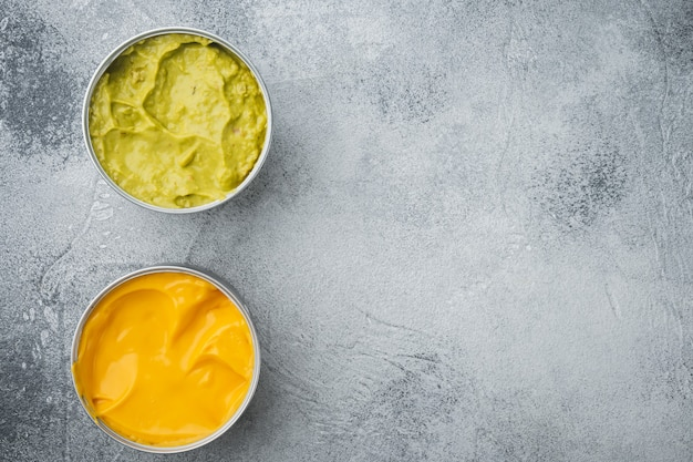 Canned cheese and guacamole  sauce in can, on gray table, top view or flat lay