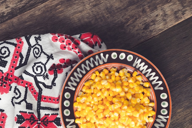 Canned corn in a brown bowl on wooden background near tablecloth.