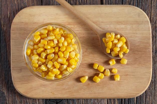 キッチンボード、トップビューでボウルにトウモロコシの粒を缶詰
