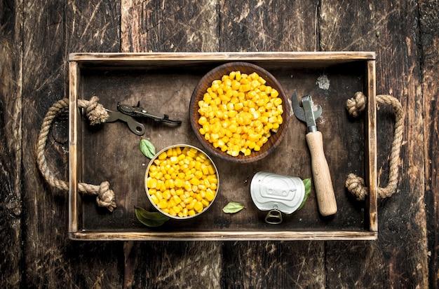 ボウルに缶詰のトウモロコシ。木製の背景に。