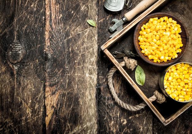 木製のテーブルの上のボウルに缶詰のトウモロコシ。
