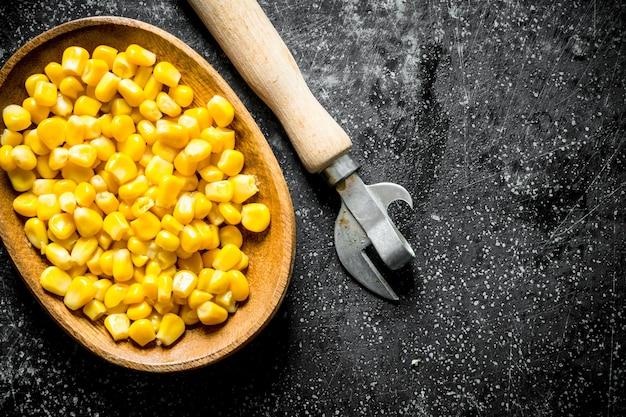 缶切りが付いている皿の上の缶詰のトウモロコシ。暗い素朴な