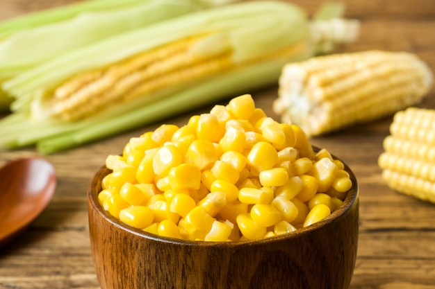 Canned corn in a wooden plate and cob of fresh corn on a rustic wooden background