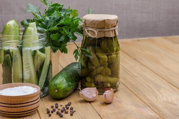 통조림 오이, 유리 항아리에 다진 오이, 소금 및 녹색 파슬리, 마늘 및 향신료. 수제 발효 제품. 건강한 겨울 음식. ight 나무 표면. 공간 복사