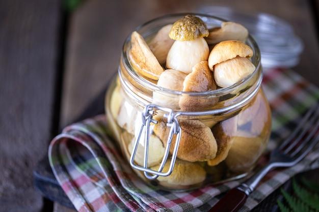 ガラスの瓶に缶詰の食用ポルチーニ茸。自家製キノコのピクルス。
