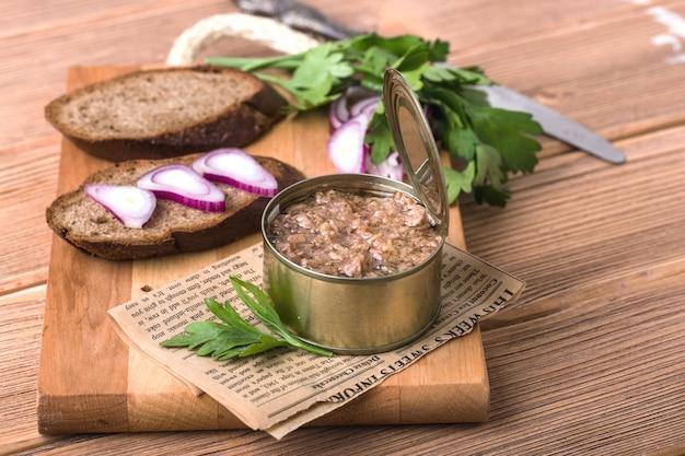 Рыбные консервы в открытой жести, два куска темного хлеба, с луком и петрушкой, на деревянной разделочной доске, коричневый фон
