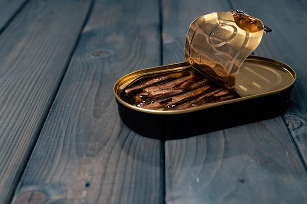 ソースの缶詰の魚は暗い木製のテーブルに保存します