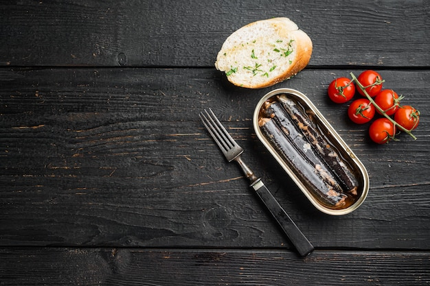 Canned fish in oil set, on black wooden table background, top view flat lay, with copy space for text