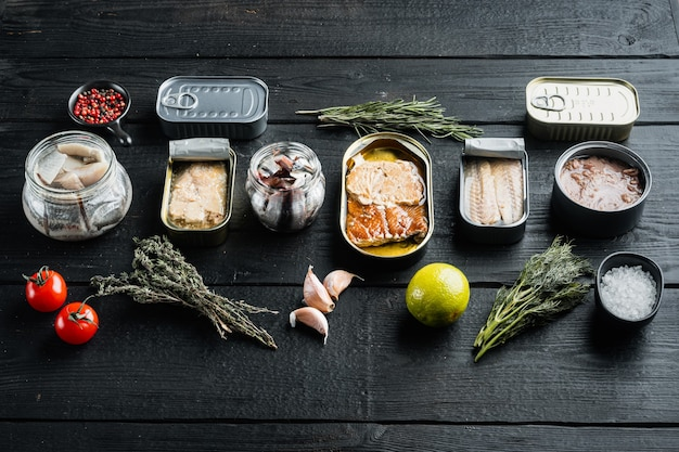 Консервы рыбные, набор лучших американских консервов, на черном деревянном столе