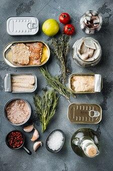 缶詰の魚、トップアメリカンプリザーブセット、ハーブと食材を含む灰色のテーブル、トップビューフラットレイ