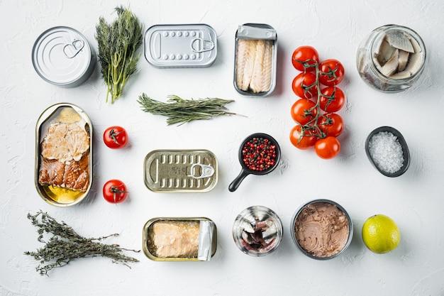Консервы рыбные, набор лучших американских консервов, на белом с травами и ингредиентами, плоский вид сверху