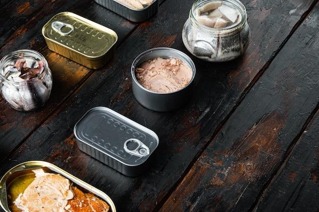 Консервы рыбные с различными видами ассортимента морепродуктов, на старом темном деревянном столе