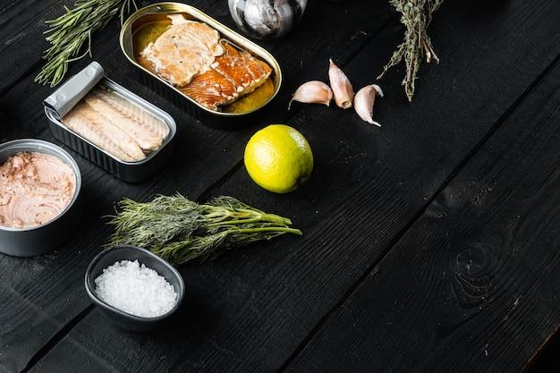Рыбные консервы с различными видами ассортимента морепродуктов, на черном деревянном столе
