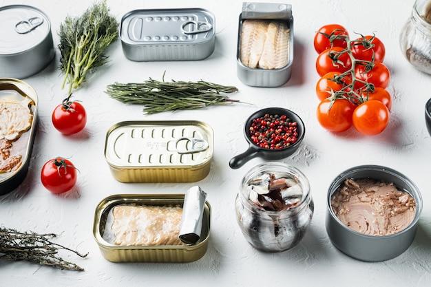 Консервы рыбные с набором морепродуктов разного ассортимента, на белом с травами и ингредиентами