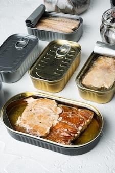 Консервы рыбные с различными типами ассортимента набора морепродуктов, на белом