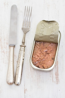 Canned fish on wooden surface
