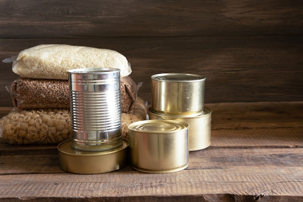 缶詰食品と暗い木製のテーブルの上の食品