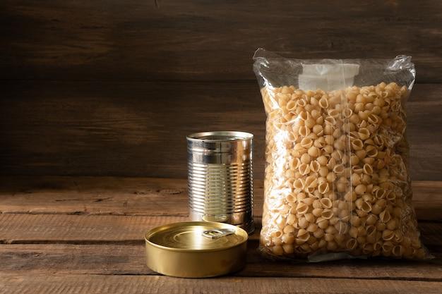 暗い木製の背景に缶詰食品とシリアルのパケット。食品ストックの概念